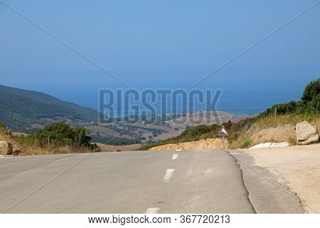 Panoama With Steep Downhill Road To The Mediterranean Sea In The French Island Corsica