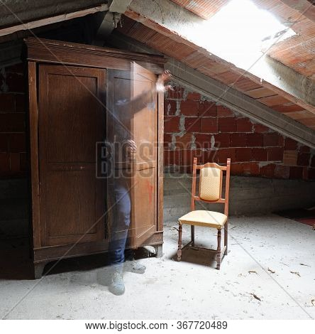 Fearful Ghost Coming Out Of The Closet Of A Dusty Attic Of An Abandoned House
