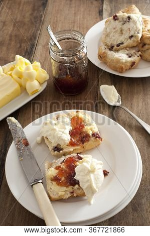 Fresh Buttered Rock Cake With A Dollop Of Whipped Cream And Fruit Jam Served On A White Plate With A