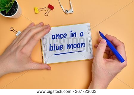 English Idiom Hand Lettering About Time - Once In A Blue Moon On Wooden Blocks. Close Up.