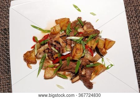 Fried Beef With Green Onion And Potatoes On The White Plate