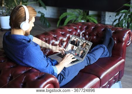 Businessman In Headphones Lying On Sofa Speak Talk On Video Call With Colleagues On Online Briefing