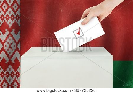 Belarusian Vote Concept. Voter Hand Holding Ballot Paper For Election Vote On Polling Station