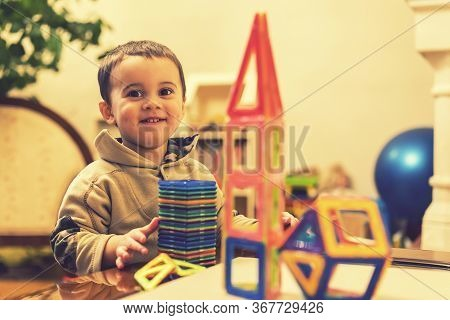 The Boy 2 Years Building A Tower From A Bright Constructor. Little Smiling Boy Playing With Magnetic