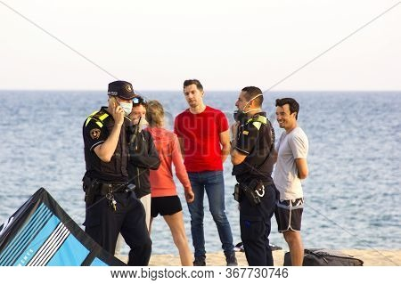 Barcelona, Spain - May 23, 2020: Police Patrolling A Beach And Talking With Kitesurf Sportsmen. Prot