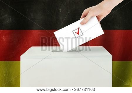 Germany Vote Concept. Voter Hand Holding Ballot Paper For Election Vote On Polling Station