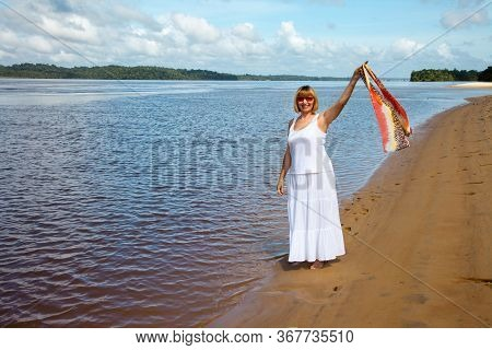 A Joyous Happy Woman In A Long White Sundress Walking Along The River Beach With A Fluttering Scarf