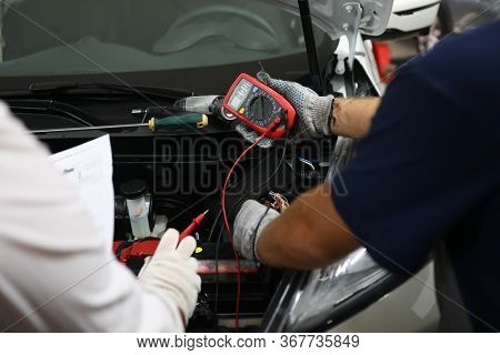 Auto Mechanic In Workshop With Diagnose Car Engine. Monitoring Battery Voltage In Real Time. Cost Au