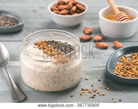Overnight Oats In Jar And Ingredients - Chia Seeds, Almond, Honey And Pollen On Gray Wooden Table Ba