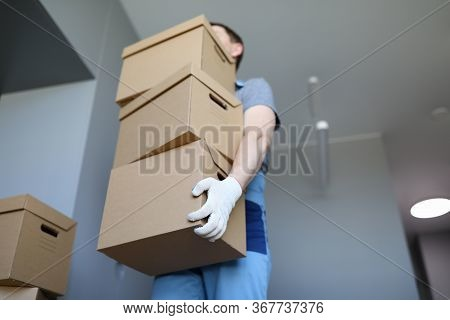 Man In Work Clothes And Gloves Carries Cardboard Boxes. Folding Boxes. Moving Waiting For Loading Se