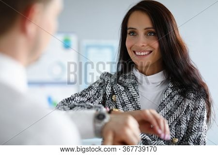Employees Man And Woman Compare Watches And Laugh. Woman Seeks To Use Qualities Employees In Differe