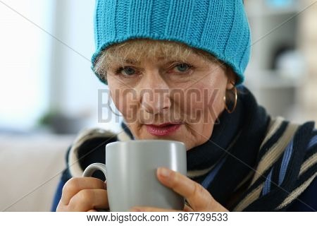Elderly Woman Feels Sick And Drinks Tea At Home. Lady In Knitted Hat Takes Cup Tea. Parents Do Not T
