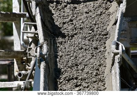 Wet Concrete Pours Down A Chute From A Ready-mix Truck At A Building Site.