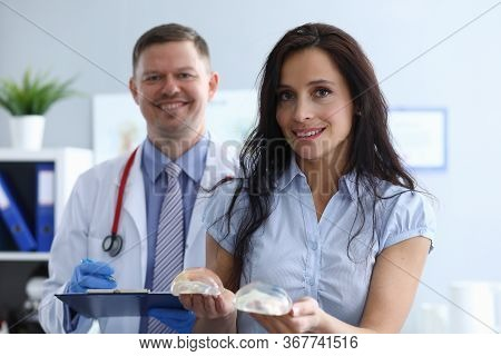 Girl In Clinic Holds Breast Implants Near Doctor. Comfortable Atmosphere. Work Plastic Surgeon. Sele