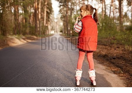 Picture Of Joyful Active Little Girl Eating Ice Cream, Rollerskating Alone, Wearing Red Suit, Having