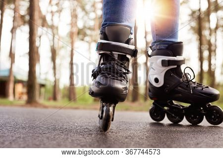 Horizontal Photo Of Modern Black Roller Skates Being On Road Outskirts, Unknown Person Riding During