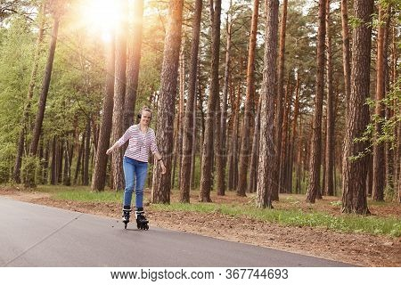 Horizontal Shot Of Active Slender Cute Young Female Rollerblading Alone, Listening To Music, Riding