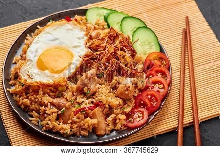 Nasi Goreng - Indonesian Chicken Fried Rice On A Black Plate On Dark Slate Backdrop. Nasi Goreng Is