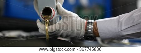 Timely Replacement Oil In Car With New One Oil. Male Hands In Protective Gloves Pour Liquid From Can