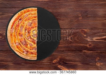 Half A Pizza With Beef Sausages, Mozzarella, Various Sauces And Marinated Red Onions On A Slate Plat