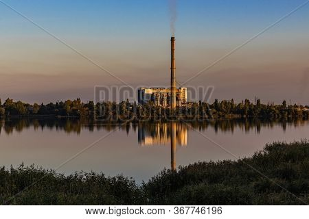 Old Garbage Incineration Plant On Lake Bank. Old Waste Incinerator Plant With Smoking Smokestack. Co