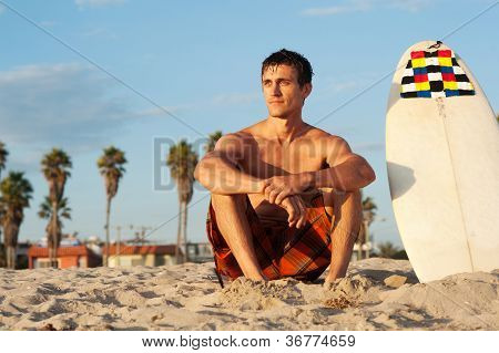Surfer Sitting On The Beach With Surfboard