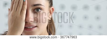 Eye Examination By Specialist In Eye Disease. Young Woman Doctor In White Coat Closes One Eye With H