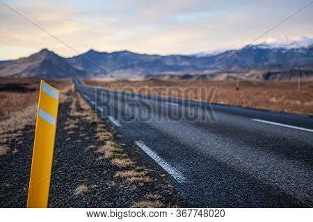 Road Number One With A Kilometer Pole In The Foreground In Iceland With Snow-capped Mountains In The