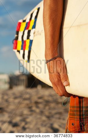 Closeup Of A Surfer Holding A Surfboard