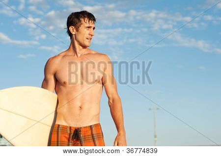 An Active Young Man With A Surfboard At The Beach