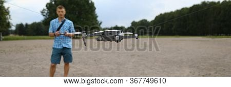 In Foreground Drone Flies, Guy Controls Drone. Geospatial Data Collection And Analysis. Help Field G