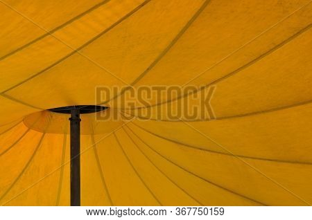 View To Seams And Metal Pole Of A Large Sunshade Awning Of Yellow Fabric