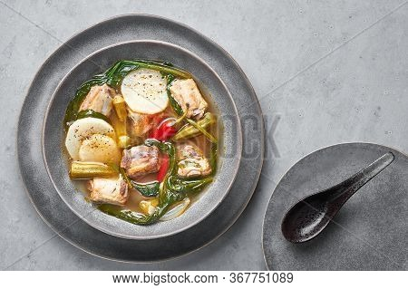 Sinigang Na Baboy Or Filipino Pork Meat Soup In Gray Bowl On Concrete Backdrop. Sinigang Is A Filipi