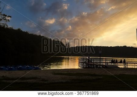 Spectacular Sunset Over The Lake Settled Deep In The Forest.