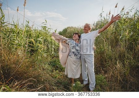 An Old Married Couple On A Summer Walk In The Field. The Couple Stand With Their Hands Up