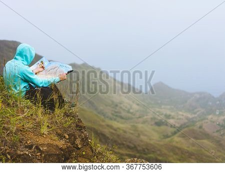 Traveler Wear Blue Hoodie With The Map Sitting On The Hill Of A Mountain In Front Of A Gorgeous Pano