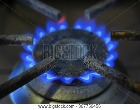 Blue Flames Of Gas Burning From A Kitchen Gas Stove. Focus The Front Edge Of The Hotplate