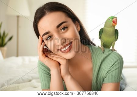 Young Woman With Alexandrine Parakeet Indoors. Cute Pet