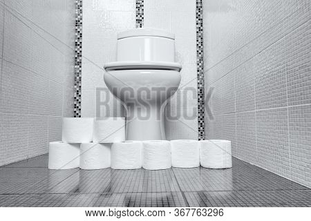 Toilet Room With White Toilet Bowl And Many Paper Rolls On A Floor. Concept Of Virus Outbreak And Pa