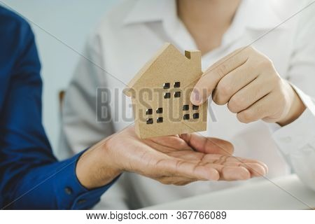 Hand Of Real Estate Broker Manager Giving House Model To Customer After Signing Contract For Buying