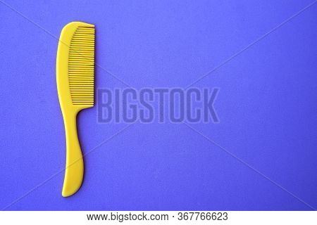 Childrens Plastic Hair Comb Yellow, Blue Background Close-up