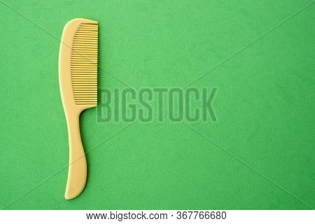 Childrens Plastic Hair Comb Yellow, Green Background Close-up