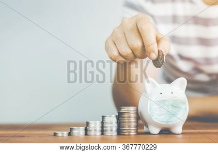 Hand Putting Coin On Piggybank In Mask With Stack Coin .saving Money Concept.