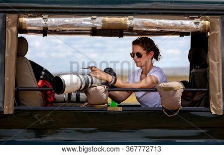 Female professional photographer on safari. Woman rests camera on a bean bag and shoots wildlife from a safari vehicle.  in the Masai Mara, Kenya. She is checking images and settings from the screen.