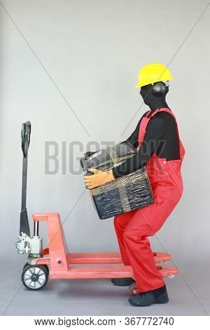 Occupational safety and health. Anonymous worker dealing with heavy package at manual pallet truck.Correct body position.