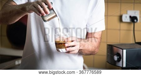Man Pouring Frothed Milk Into Espresso For Making A Latte Cappuccino Coffee. Home Barista Indoors Li
