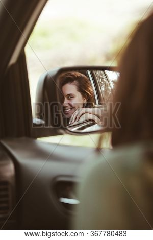 Reflection On Stunning Smiling Woman In Car Rear Mirror