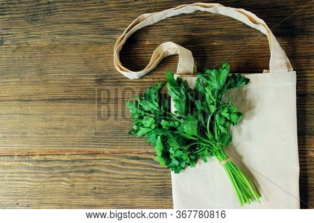 Eco Bag And Bunch Of Parsley On A Wooden Background. Eco Bag Of Cotton On Brown Wooden Background. Z