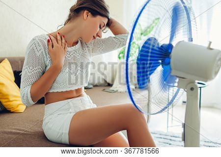 Summer Heat. Air Conditioning. Young Woman Cooling Down Feeling Hot Sitting On Couch By Ventilator A