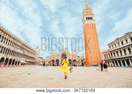 Woman In Elegance Yellow Sundress With Straw Bag Walking By Venice Saint Marco Square